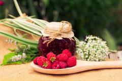 Fresh raspberries and jam on wooden table. Selective focus Royalty Free Stock Images