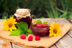 Fresh raspberries and jam on wooden table. Selective focus Stock Photos