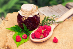 Fresh raspberries and jam on wooden table. Selective focus Royalty Free Stock Photos