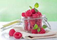 Fresh raspberries. In a jar on the table close-up Stock Images