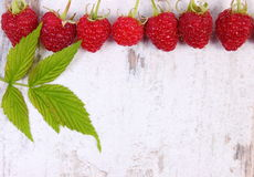 Fresh raspberries with leaf and copy space for text on old wooden background Stock Photos