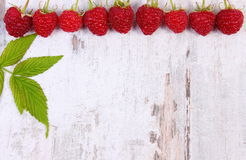 Fresh raspberries with leaf and copy space for text on old wooden background Royalty Free Stock Images
