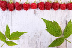 Fresh raspberries with leaf and copy space for text on old wooden background Royalty Free Stock Image
