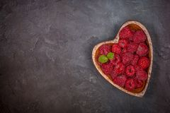 Fresh raspberries with a leaf of mint in the heart-shaped bowl on a dark black background. Flat lay Royalty Free Stock Photography