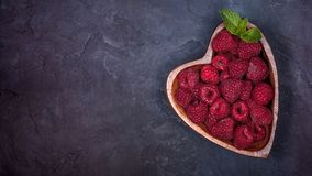 Fresh raspberries with a leaf of mint in the heart-shaped bowl on a dark blue background. Flat lay Stock Photos