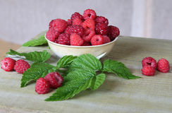Fresh raspberries with leaves in the Cup. Cup with raspberries on a old wooden background Stock Image