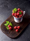 Raspberries in cup on on a black background. Fresh raspberries with leaves in cup on wood  on black background Stock Photo