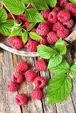 Fresh raspberries with leaves. Ripe fresh raspberries with leaves on rustic wooden background. Healthy eating antioxidant nutrition concept Stock Photo