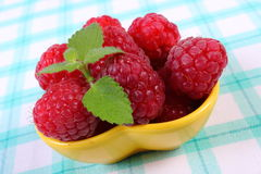 Fresh raspberries and lemon balm on checkered tablecloth, healthy food. Fresh raspberries and leaf of lemon balm on checkered tablecloth, concept of healthy food Stock Image
