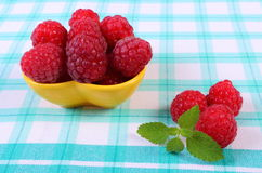 Fresh raspberries and lemon balm on checkered tablecloth, healthy food. Fresh raspberries and leaf of lemon balm on checkered tablecloth, concept of healthy food Royalty Free Stock Image