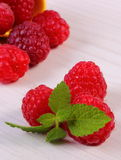 Fresh raspberries and lemon balm on white wooden table, healthy food Stock Image