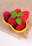Fresh raspberries and lemon balm on white wooden table, healthy food Stock Photo