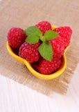 Fresh raspberries and lemon balm on white wooden table, healthy food. Fresh raspberries and leaf of lemon balm in yellow bowl on white wooden table, concept of Stock Photo
