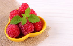 Fresh raspberries and lemon balm on white wooden table, healthy food Royalty Free Stock Image