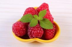Fresh raspberries and lemon balm on white wooden table, healthy food. Fresh raspberries and leaf of lemon balm in yellow bowl on white wooden table, concept of Stock Images
