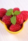 Fresh raspberries and lemon balm on white wooden table, healthy food. Fresh raspberries and leaf of lemon balm in yellow bowl on white wooden table, concept of Stock Image