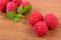 Fresh raspberries and lemon balm on wooden surface, healthy food Royalty Free Stock Images