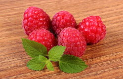 Fresh raspberries and lemon balm on wooden surface, healthy food Royalty Free Stock Photo