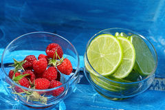 Fresh raspberries and lime in a jar on blue background.  Royalty Free Stock Images
