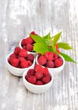 Fresh raspberries in little bowls. With leaf on a white wooden table Stock Photo