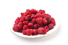 Fresh raspberries lying on a white plate. On a white background Royalty Free Stock Image