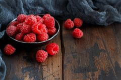 Fresh raspberries in a bowl. Fresh raspberries in a metal bowl on a wooden background Stock Photos