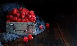 Fresh raspberries in a box. Fresh raspberries in a metal box on a dark background close up Stock Photos