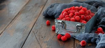 Fresh raspberries in a box. Fresh raspberries in a metal box on a wooden table Royalty Free Stock Photos