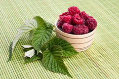 Fresh raspberries with mint in a bowl. On White wooden table Royalty Free Stock Photos