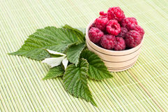 Fresh raspberries with mint in a bowl. On White wooden table Royalty Free Stock Photo