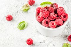 Fresh raspberries with mint. In small bowl, on grey stone background, copy space Royalty Free Stock Image