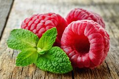 Fresh raspberries with mint. On a wood background. toning. selective focus Royalty Free Stock Photo