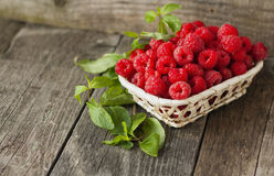Fresh raspberries and mint horizontal. Fresh raspberries and mint in a basket on a wooden background, horizontal Stock Image