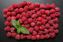 Fresh raspberries with mint leaf. On black background Royalty Free Stock Photos
