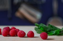 Fresh raspberries and mint leaves. On wooden cutting board Stock Photo