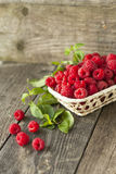 Fresh raspberries and mint on a wooden background. Fresh raspberries and mint in a basket on a wooden background Royalty Free Stock Photography