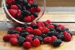 Fresh raspberries and mulberries. Fresh red raspberries and black mulberries on a wooden table Stock Photo
