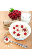 Fresh raspberries, Oatmeal flakes and milk on a wooden table. Stock Photography