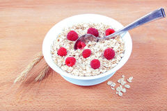 Fresh raspberries, Oatmeal flakes on a wooden table. Healthy food Royalty Free Stock Photos