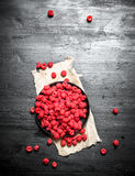 Fresh raspberries in the old plate. On a black wooden background Royalty Free Stock Image