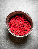 Fresh raspberries in the old pot. On a stone background Stock Image