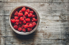 Fresh raspberries. On old wooden surface. Toned photo Stock Photo