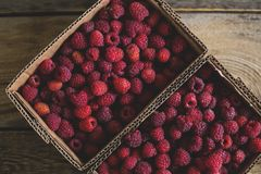 Fresh raspberries in paper boxes. On a wooden background Royalty Free Stock Photos