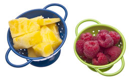 Fresh Raspberries and Pineapples. In vibrant colanders isolated on white with a clipping path Royalty Free Stock Photos