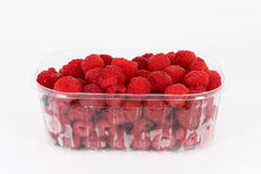 Fresh raspberries in plastic container. On white background Royalty Free Stock Image