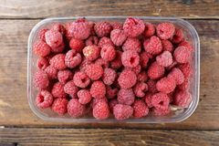 Fresh raspberries in a plastic container on a wooden background. Space for text Royalty Free Stock Photo
