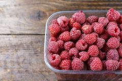 Fresh raspberries in a plastic container on a wooden background. Space for text Stock Image