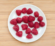 Fresh Raspberries In Plate On Counter. Overhead view of fresh raspberries in plate on counter Stock Photography