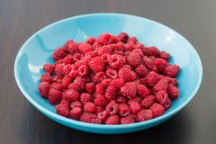 Fresh raspberries in a  plate. Fresh raspberries in a large blue plate Royalty Free Stock Images