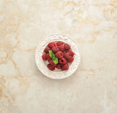 Fresh raspberries on a plate on a marble background Stock Images